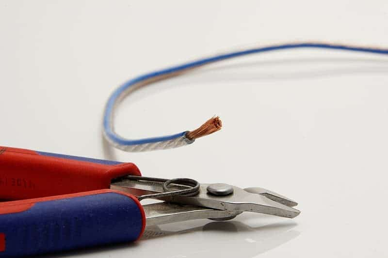 A pair of pliers next to a stripped wire