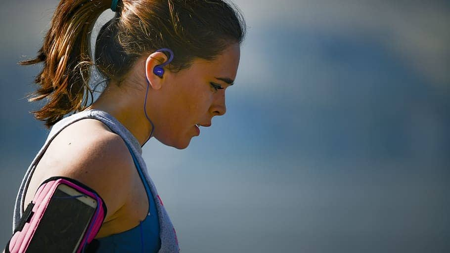 Woman exercising while wearing in-ear headphones
