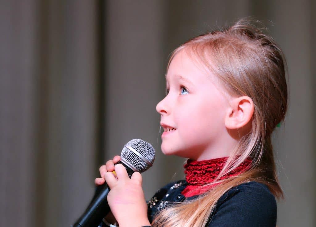 An Adolescent Girl with a Mic in Her Hand