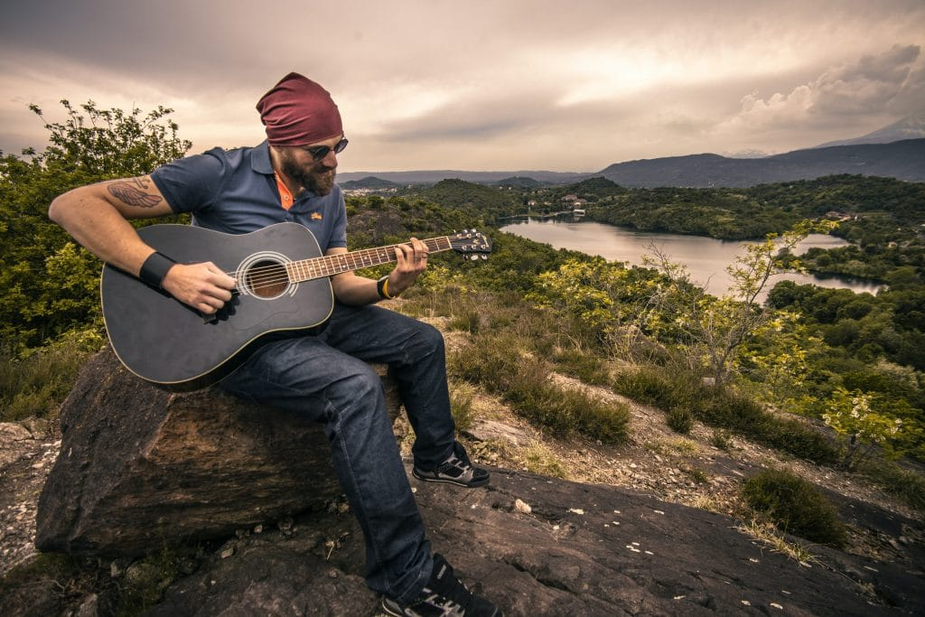 A Man Playing a Guitar on The Mountains